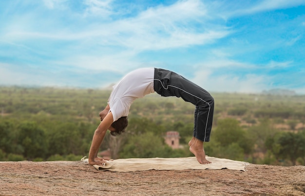 Junger indischer mann oben auf berg, der in yoga-haltung sitzt.