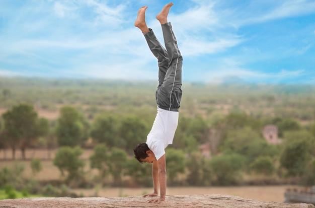Junger indischer mann oben auf berg in adho mukha vrksasana yoga pose.