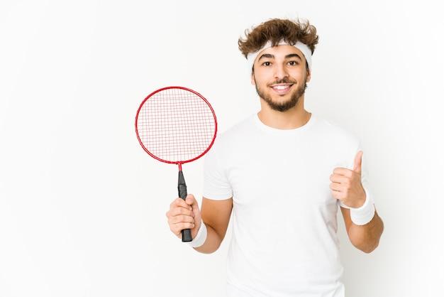 Junger indischer mann spielt badminton lächelnd und hebt daumen hoch