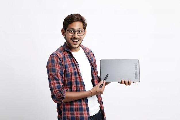 Junger indischer professioneller designer, der grafiktablett mit digitalem stift zeigt