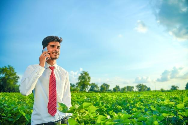 Junger indischer schöner agronom, der auf smartphone am feld spricht