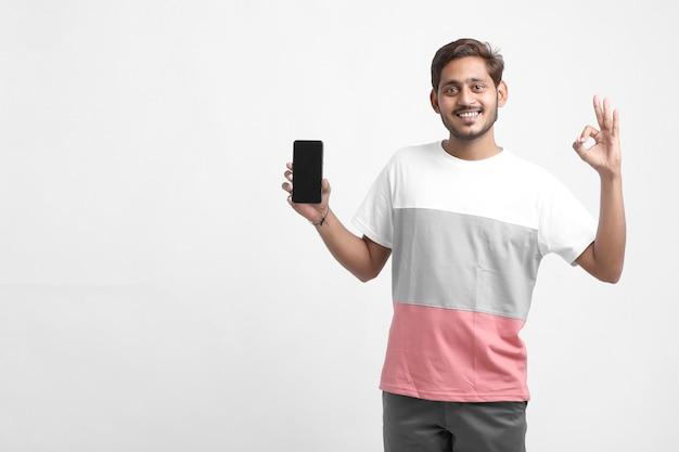 Junger indischer student, der smartphone-bildschirm zeigt