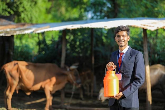 Junger indischer tierhaltungsoffizier, der milchflasche in der hand auf milchfarm hält