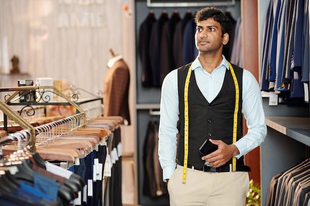 Junger indischer verkaufsleiter mit maßband, der in einem bekleidungsgeschäft für männer arbeitet?