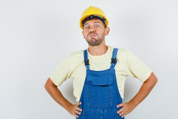 Junger ingenieur bläst wangen mit händen auf taille in uniform und sieht verwirrt aus. vorderansicht.