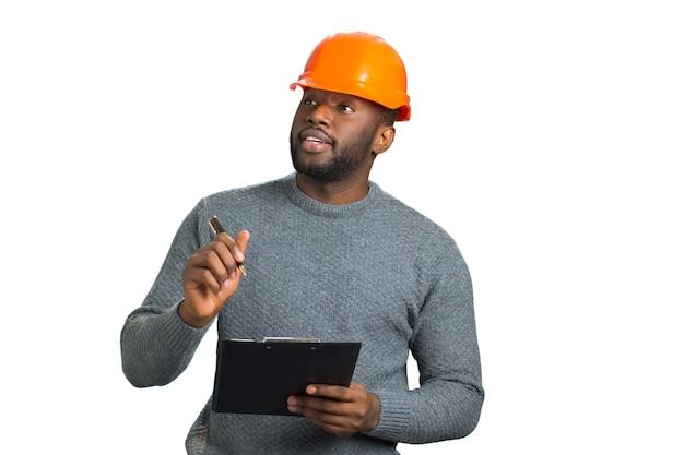 Junger ingenieur, der bau inspiziert. hübscher afroamerikanischer architekt mit zwischenablage nah oben