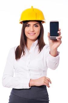 Junger ingenieur, der ein smartphone vorstellt