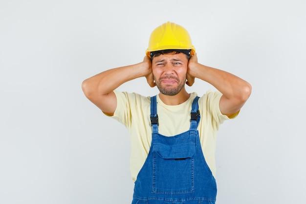 Junger ingenieur, der hände auf ohren in uniform hält und genervte vorderansicht schaut.