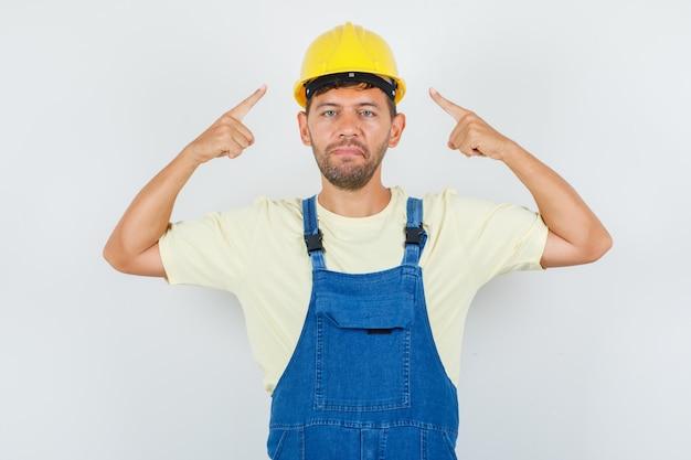Junger ingenieur, der in uniform auf seinen helm zeigt und selbstbewusst aussieht, vorderansicht.