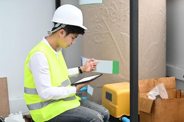 Junger ingenieur, der tablette beim sitzen am baustellenprojekt verwendet.