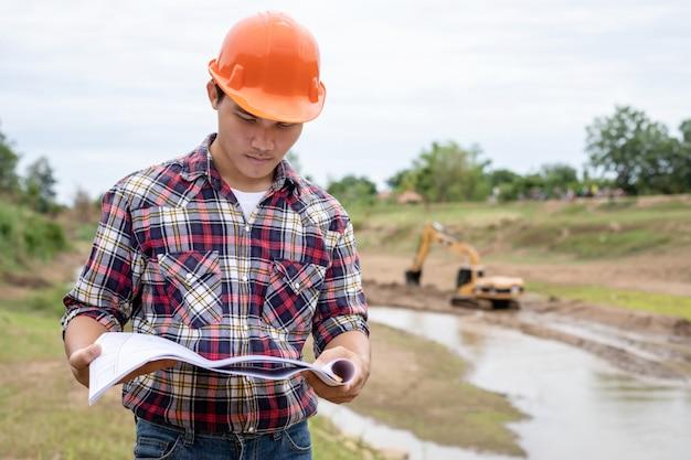 Junger ingenieur, der vor ort an der verdammung arbeitet