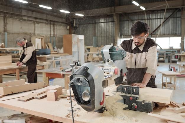 Junger ingenieur der zeitgenössischen möbelfabrik, der elektrische kreissäge verwendet, um dickes holzbrett zu schneiden, während er sich über werkbank beugt