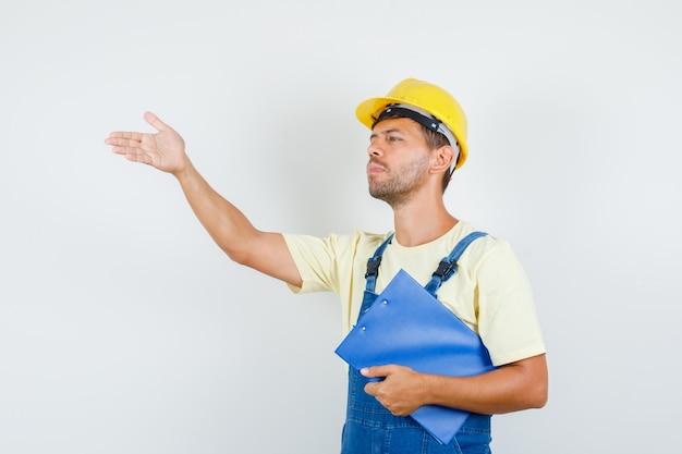 Junger ingenieur, der zwischenablage hält und anweisungen in der einheitlichen vorderansicht gibt.