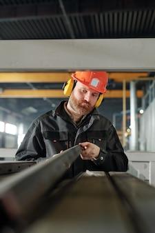 Junger ingenieur einer industrieanlage, der eines der eisendetails betrachtet, während er seine eigenschaften durch arbeitsplatz untersucht