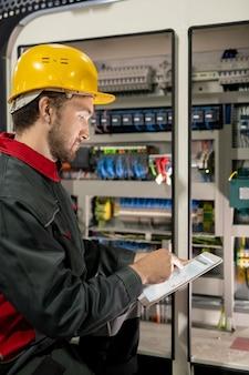 Junger ingenieur in arbeitskleidung und bauarbeiterhelm, der auf eine elektronische skizze oder ein schema in einem tablet zeigt, während er an einer der industriemaschinen hockt