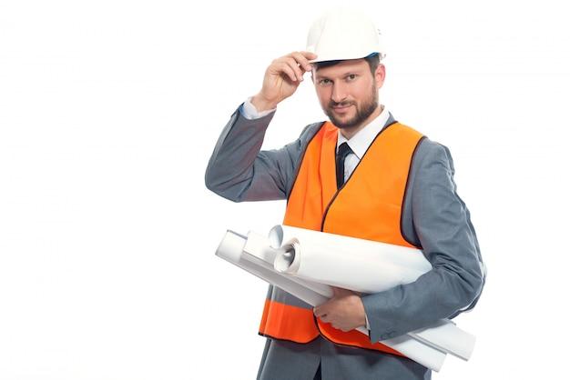 Junger ingenieur lächelnd, weißen sicherheitshut durch hand haltend.