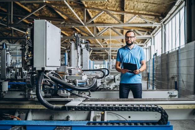 Junger ingenieur manager mit bart, der manufaktur, arbeitsplatz und maschinen auf großer fabrik prüft.