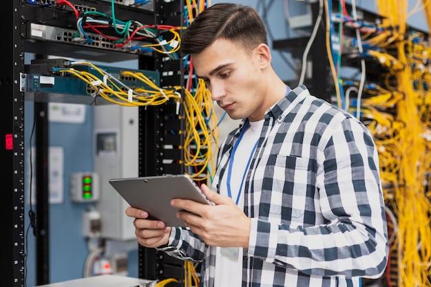 Junger ingenieur mit einer tablette im mittleren schuss des serverraumes