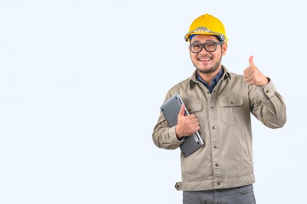 Junger ingenieur mit laptop und gelbem schutzhelm