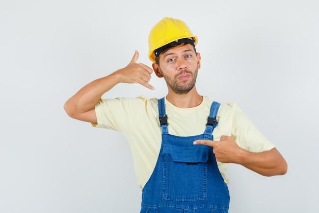 Junger ingenieur zeigt ein rufzeichen in einheitlicher vorderansicht.