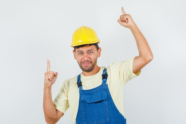 Junger ingenieur zeigt nach oben und lächelt in uniform, vorderansicht.