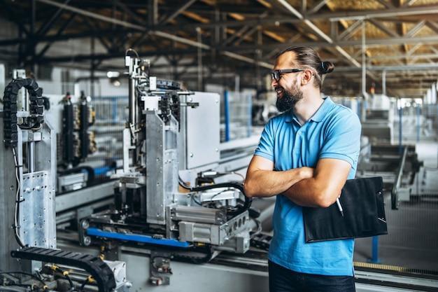 Junger ingenieurmanager mit bart manufaktur, arbeitsplatz und maschinerie in der großen fabrik überprüfend.