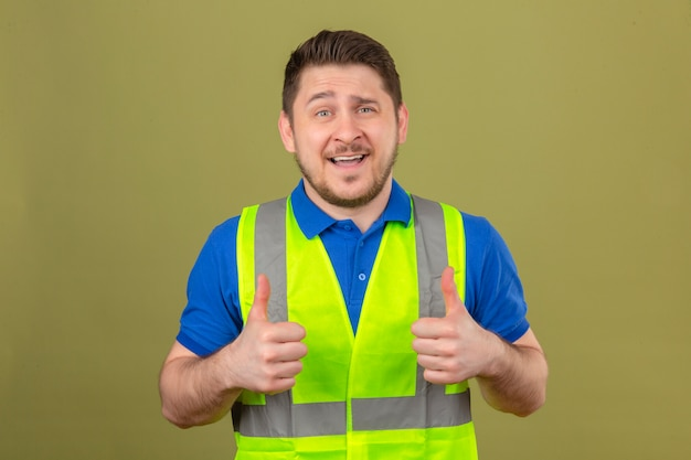 Junger ingenieurmann, der bauweste trägt, die kamera mit großem lächeln und glücklichem gesicht betrachtet, das daumen oben über lokalisiertem grünem hintergrund zeigt