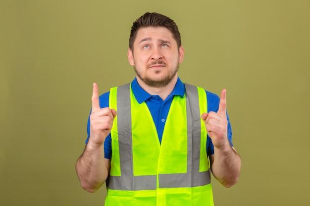 Junger ingenieurmann, der bauweste trägt, die oben zeigende finger mit skeptischem lächeln auf gesicht über lokalisiertem grünem hintergrund nach oben zeigt