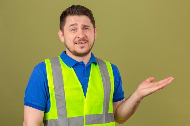 Junger ingenieurmann, der konstruktionsweste trägt, die kamera betrachtet und mit handfläche steht, die über lokalisiertem grünem hintergrund steht