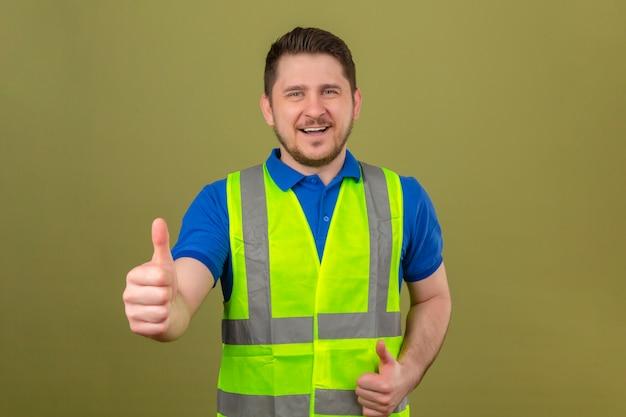 Junger ingenieurmann, der konstruktionsweste trägt, die kamera mit großem lächeln und glücklichem gesicht betrachtet, das daumen oben über lokalisiertem grünem hintergrund zeigt