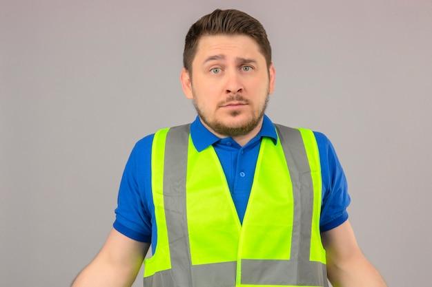 Junger ingenieurmann, der konstruktionsweste trägt, die verwirrt schaut und keine ahnung hat, was zu tun ist, über lokalisiertem weißem hintergrund zu stehen