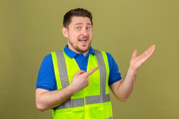 Junger ingenieurmann, der konstruktionsweste trägt, die zur kamera lächelt, während mit hand präsentiert und mit finger über lokalisiertem grünem hintergrund zeigt