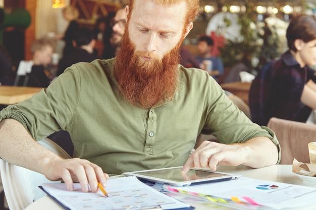 Junger ingwermann, der tablette im café verwendet