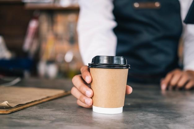 Junger inhaber des kaffeecaféservicekunden.