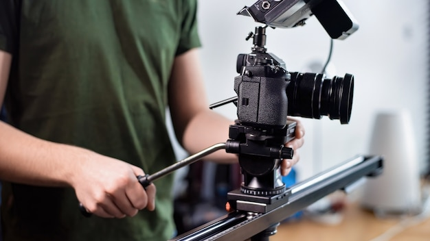 Junger inhaltsschöpfermann, der mit kamera auf schieberegler, professionelles rig filmt