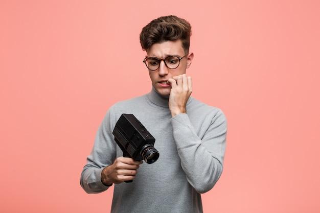 Junger intellektueller mann, der beißende fingernägel einer filmkamera hält, nervös und sehr besorgt.