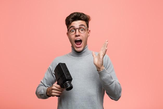 Junger intellektueller mann, der eine filmkamera feiert einen sieg oder einen erfolg hält