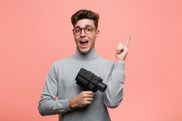 Junger intellektueller mann, der eine filmkamera lächelt hält, freundlich zeigend mit dem zeigefinger weg.