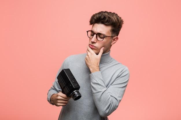 Junger intellektueller mann, der eine filmkamera seitlich schaut mit zweifelhaftem und skeptischem ausdruck hält.