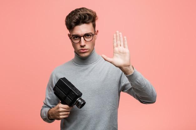 Junger intellektueller mann, der eine filmkamera steht mit der ausgestreckten hand zeigt das stoppschild und verhindert sie hält.