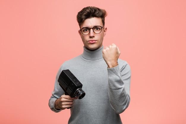 Junger intellektueller mann, der eine filmkamera zeigt faust zur kamera, aggressiver gesichtsausdruck hält.