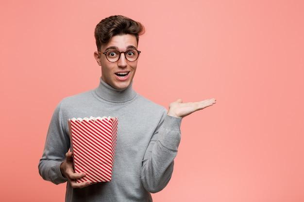 Junger intellektueller mann, der einen popcorneimer nett und überzeugt hält, okaygeste zeigend.