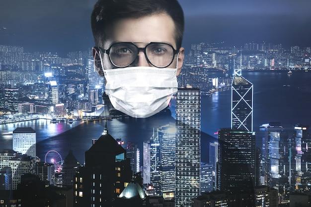 Junger intelligenter mann mit gesichtsmaske gegen die stadt
