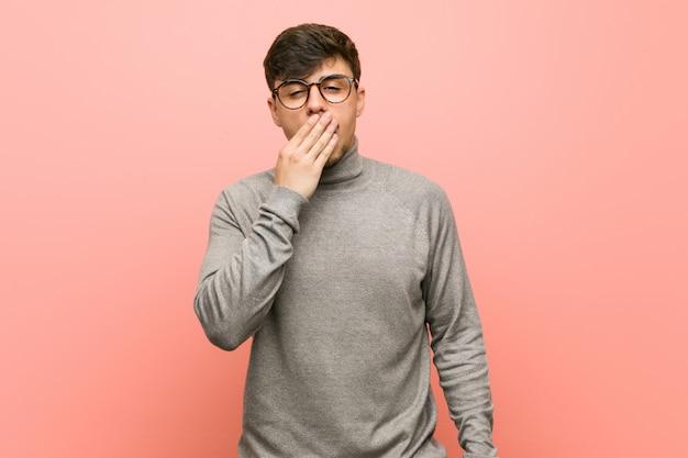 Junger intelligenter studentenmann, der eine müde geste bedeckt mund mit der hand zeigend gähnt.