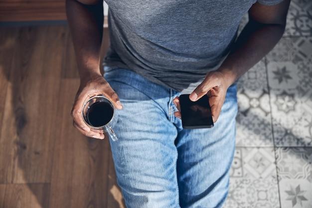 Junger internationaler mann, der eine tasse mit kaffee in der hand hält, während er online-nachrichten liest