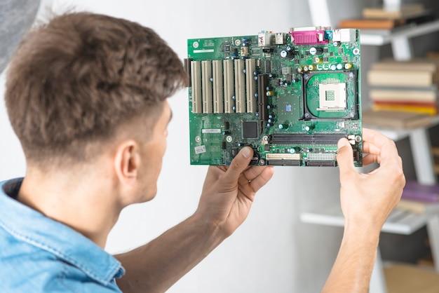 Junger it-techniker, der motherboard betrachtet