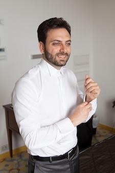 Junger italienischer bräutigam mit bart, braunen haaren und grünen augen vor der ehe