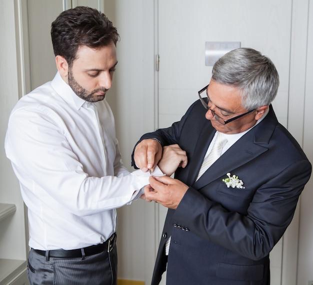 Junger italienischer bräutigam mit seinem vater vor der heirat