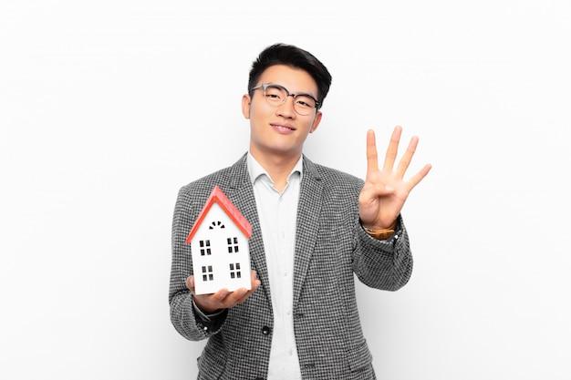 Junger japanischer mann, der freundlich lächelt und schaut, nummer vier oder vierten mit der hand vorwärts zeigend, mit einem hausmodell herunterzählend