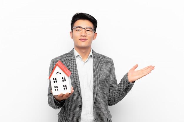 Junger japanischer mann, der fröhlich lächelt, sich glücklich fühlt und ein konzept im kopierraum mit handfläche mit einem hausmodell zeigt